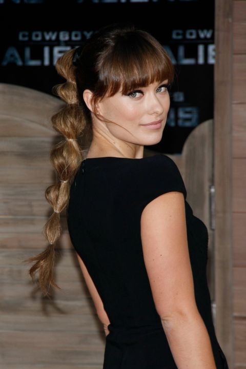 To recreate Olivia Wilde's cool take on a classic pony, pull your hair up at the crown of your head and secure it with a clear elastic band. Next, section off 1.5-inch sections with clear elastics all the way down your ponytail. Then, pouf out each section of hair by gently pulling on it to create the bubble effect.