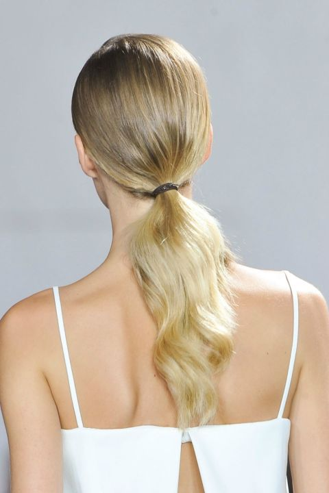 Textured hair is still on trend, so to wear this wavy style, simply brush your hair back away from your face before pulling it into a low pony. Next, add a few loose waves by holding a 1-inch curling iron perpendicular to your hair and wrapping sections around the barrel. Then, hit the tail with some salt spray to give it a beachy look.