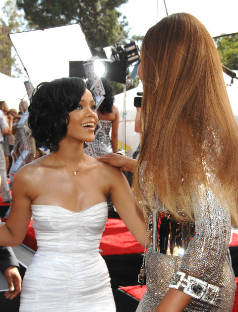 Rihanna lights up in front of Beyoncé during their first photographed appearance together at the 2007 BET Awards.