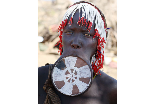 The Mursi Women of Southern Ethopia insert clay plates into their lower lips to stretch them out, increasing the size of a plate incrementally to make their pouts ginormous. This ritual is a symbol of both sexual maturity and beauty.